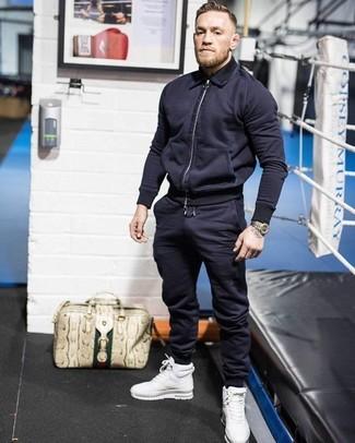 Wie kombinieren: dunkelblaue Bomberjacke, dunkelblaue Jogginghose, weiße hohe Sneakers aus Leder, hellbeige Shopper Tasche aus Leder