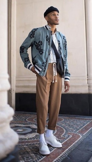 Wie kombinieren: hellblaue bedruckte Bomberjacke, hellblaues vertikal gestreiftes Langarmhemd, braune Anzughose, weiße Leder Derby Schuhe
