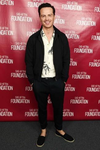 Andrew Scott trägt schwarze Wollbomberjacke, weißes und schwarzes bedrucktes Langarmhemd, schwarze Chinohose, schwarze Segeltuch Espadrilles