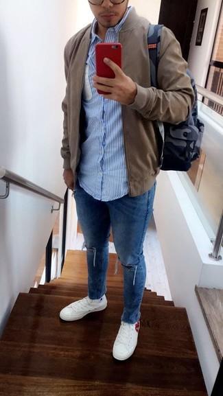 Wie kombinieren: olivgrüne Bomberjacke, hellblaues vertikal gestreiftes Langarmhemd, blaue enge Jeans mit Destroyed-Effekten, weiße Segeltuch niedrige Sneakers
