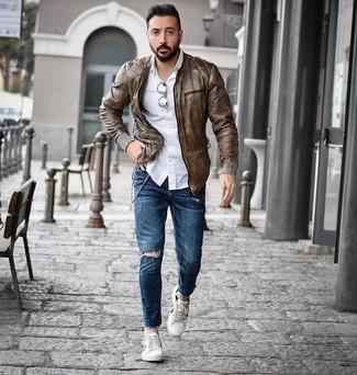 Wie kombinieren: braune Leder Bomberjacke, weißes Langarmhemd, blaue enge Jeans mit Destroyed-Effekten, weiße niedrige Sneakers