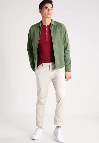 Wie kombinieren: olivgrüne Bomberjacke, rotes T-shirt mit einer Knopfleiste, hellbeige Chinohose, weiße Sportschuhe
