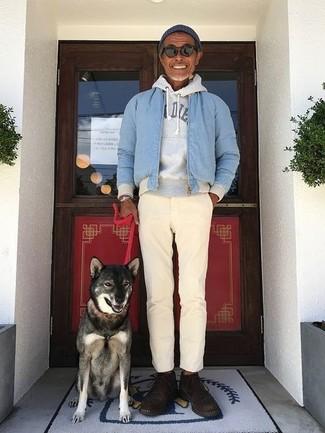 Wie kombinieren: hellblaue Bomberjacke, grauer bedruckter Pullover mit einem Kapuze, hellbeige Chinohose, dunkelbraune Chukka-Stiefel aus Wildleder