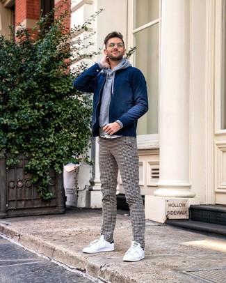dunkelblaue Bomberjacke, grauer Pullover mit einem Kapuze, weiße und schwarze Chinohose mit Vichy-Muster, weiße niedrige Sneakers für Herren