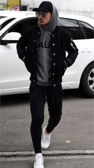 Wie kombinieren: schwarze Bomberjacke, grauer bedruckter Pullover mit einem Kapuze, schwarze Jogginghose, weiße Leder niedrige Sneakers