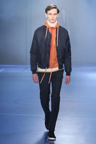 schwarze Bomberjacke, orange Pullover mit einem Kapuze, weißer Rollkragenpullover, schwarze Chinohose für Herren