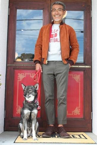 Wie kombinieren: rotbraune Wildleder Bomberjacke, weißes und rotes bedrucktes T-Shirt mit einem Rundhalsausschnitt, graue Chinohose, dunkelrote Chukka-Stiefel aus Wildleder
