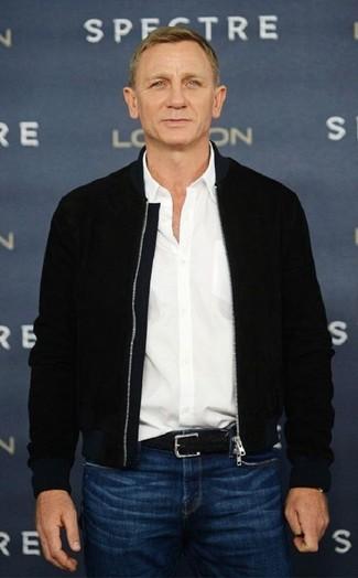 Daniel Craig trägt Schwarze Bomberjacke, Weißes Langarmhemd, Blaue Jeans, Schwarzer geflochtener Ledergürtel