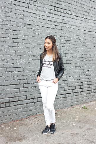Wie kombinieren: schwarze Leder Bomberjacke, graues bedrucktes T-Shirt mit einem Rundhalsausschnitt, weiße Jeans, schwarze Sportschuhe