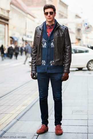 Wie kombinieren: dunkelbraune Leder Bomberjacke, dunkelblaue und weiße Strickjacke mit einem Schalkragen mit Fair Isle-Muster, dunkelblaues und rotes Flanell Langarmhemd mit Schottenmuster, dunkelblaue enge Jeans