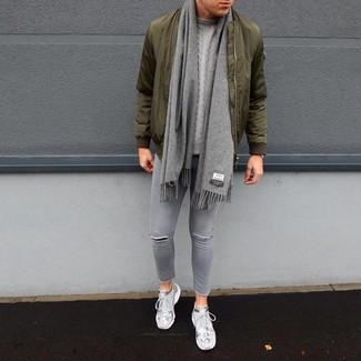 Wie kombinieren: olivgrüne Bomberjacke, grauer Strickpullover, graue enge Jeans mit Destroyed-Effekten, graue Sportschuhe