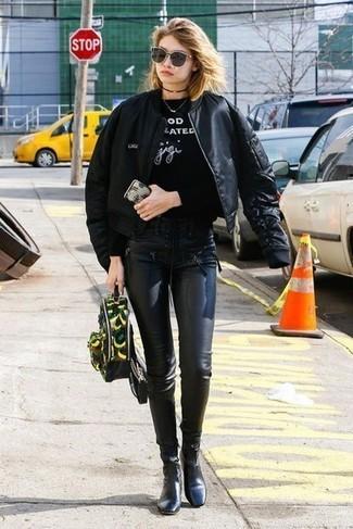 Wie kombinieren: schwarze Bomberjacke, schwarzes und weißes bedrucktes Sweatshirt, schwarze Lederleggings, schwarze Leder Stiefeletten