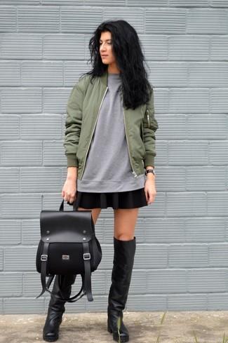 Schwarze kniehohe Stiefel aus Leder kombinieren – 35 Casual Damen Outfits: Probieren Sie diese Kombination aus einer olivgrünen Bomberjacke und einem schwarzen Skaterrock und Sie werden überall und zu jeder Zeit schick aussehen. Fügen Sie schwarzen kniehohe Stiefel aus Leder für ein unmittelbares Style-Upgrade zu Ihrem Look hinzu.