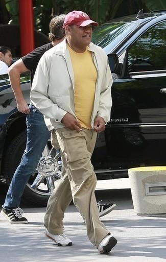 Wie kombinieren: weiße Bomberjacke, gelbes T-Shirt mit einem Rundhalsausschnitt, hellbeige Cargohose, weiße Sportschuhe