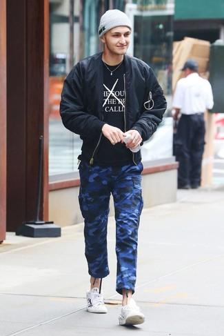 Wie kombinieren: schwarze Bomberjacke, schwarzes und weißes bedrucktes T-Shirt mit einem Rundhalsausschnitt, blaue Camouflage Cargohose, weiße bedruckte Leder niedrige Sneakers