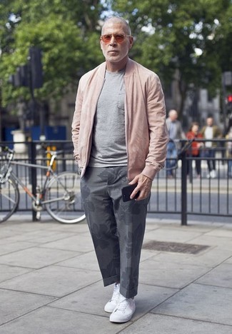 Wie kombinieren: rosa Bomberjacke, graues T-Shirt mit einem Rundhalsausschnitt, graue Chinohose mit Blumenmuster, weiße Segeltuch niedrige Sneakers