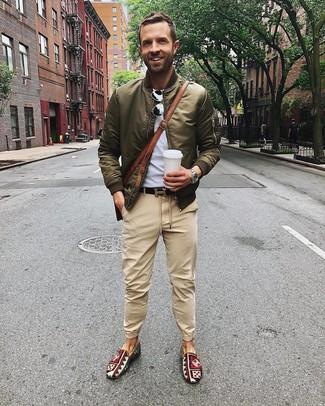Wie kombinieren: olivgrüne Bomberjacke, graues T-Shirt mit einem Rundhalsausschnitt, beige Chinohose, mehrfarbige bedruckte Slip-On Sneakers aus Segeltuch