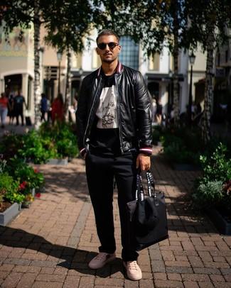Wie kombinieren: schwarze Leder Bomberjacke, schwarzes und weißes bedrucktes T-Shirt mit einem Rundhalsausschnitt, schwarze Chinohose, weiße bedruckte Leder niedrige Sneakers