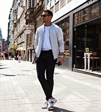 Wie kombinieren: graue Bomberjacke, weißes T-Shirt mit einem Rundhalsausschnitt, schwarze Chinohose, weiße bedruckte Leder niedrige Sneakers