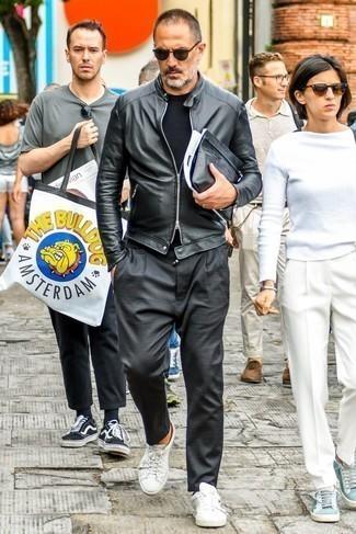 Schwarzes T-Shirt mit einem Rundhalsausschnitt kombinieren: trends 2020: Paaren Sie ein schwarzes T-Shirt mit einem Rundhalsausschnitt mit einer dunkelgrauen Chinohose für ein bequemes Outfit, das außerdem gut zusammen passt. Weiße Leder niedrige Sneakers sind eine perfekte Wahl, um dieses Outfit zu vervollständigen.