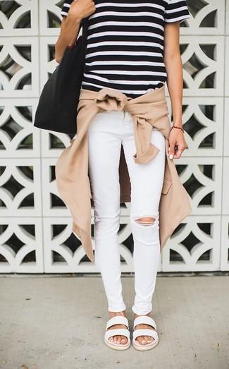 Wie kombinieren: beige Bomberjacke, schwarzes und weißes horizontal gestreiftes T-Shirt mit einem Rundhalsausschnitt, weiße enge Jeans mit Destroyed-Effekten, weiße flache Sandalen aus Leder