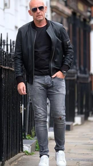 Wie kombinieren: schwarze Leder Bomberjacke, schwarzes T-Shirt mit einem Rundhalsausschnitt, graue enge Jeans mit Destroyed-Effekten, weiße Leder niedrige Sneakers