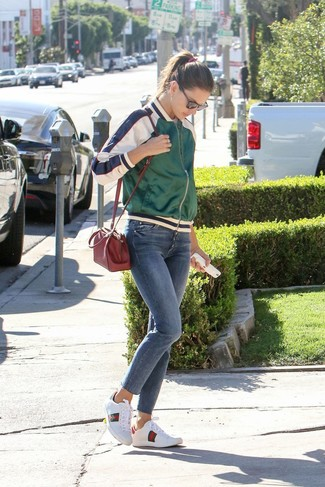 Wie kombinieren: grüne Satin Bomberjacke, weißes T-Shirt mit einem Rundhalsausschnitt, blaue enge Jeans, weiße bedruckte Leder niedrige Sneakers