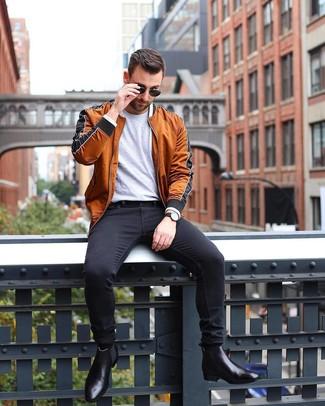 Wie kombinieren: rotbraune Bomberjacke, graues T-Shirt mit einem Rundhalsausschnitt, schwarze enge Jeans, schwarze Chelsea-Stiefel aus Leder