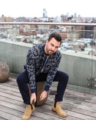 Wie kombinieren: dunkelblaue Bomberjacke mit Blumenmuster, graues T-Shirt mit einem Rundhalsausschnitt, dunkelblaue enge Jeans, beige Chelsea-Stiefel aus Wildleder