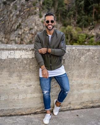 Wie kombinieren: olivgrüne Bomberjacke, weißes T-Shirt mit einem Rundhalsausschnitt, blaue enge Jeans mit Destroyed-Effekten, weiße niedrige Sneakers