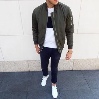 Wie kombinieren: olivgrüne Bomberjacke, weißes und schwarzes T-Shirt mit einem Rundhalsausschnitt, schwarze enge Jeans, weiße niedrige Sneakers