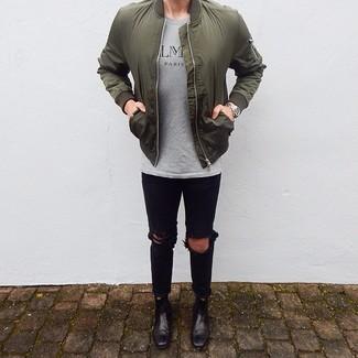 Wie kombinieren: olivgrüne Bomberjacke, graues bedrucktes T-Shirt mit einem Rundhalsausschnitt, schwarze enge Jeans mit Destroyed-Effekten, schwarze Chelsea-Stiefel aus Leder
