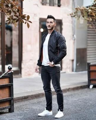 Schwarze Bomberjacke kombinieren: trends 2020: Kombinieren Sie eine schwarze Bomberjacke mit dunkelgrauen Jeans für ein bequemes Outfit, das außerdem gut zusammen passt. Weiße Segeltuch niedrige Sneakers sind eine ideale Wahl, um dieses Outfit zu vervollständigen.