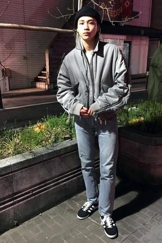 Teenager: Graue Bomberjacke kombinieren – 3 Herren Outfits: Kombinieren Sie eine graue Bomberjacke mit hellblauen Jeans, um einen lockeren, aber dennoch stylischen Look zu erhalten. Schwarze und weiße Segeltuch niedrige Sneakers sind eine perfekte Wahl, um dieses Outfit zu vervollständigen.