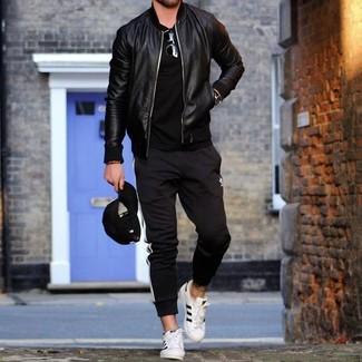 Wie kombinieren: schwarze Leder Bomberjacke, schwarzes T-Shirt mit einem Rundhalsausschnitt, schwarze und weiße vertikal gestreifte Jogginghose, weiße Leder niedrige Sneakers