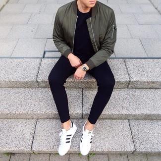 Wie kombinieren: dunkelgrüne Bomberjacke, schwarzes T-Shirt mit einem Rundhalsausschnitt, schwarze Jogginghose, weiße und schwarze Leder niedrige Sneakers