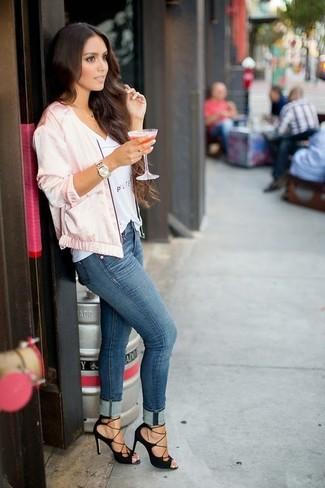Wie kombinieren: rosa Satin Bomberjacke, weißes bedrucktes T-Shirt mit einem V-Ausschnitt, blaue enge Jeans, schwarze Wildleder Sandaletten