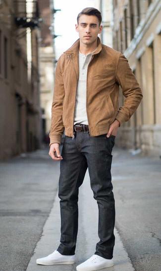 Wie kombinieren: braune Wildleder Bomberjacke, hellbeige T-shirt mit einer Knopfleiste, schwarze Jeans, weiße Segeltuch niedrige Sneakers