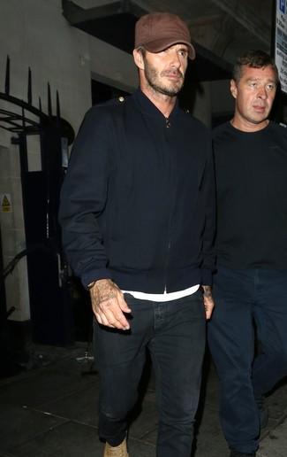 David Beckham trägt Dunkelblaue Bomberjacke, Weißes T-Shirt mit Rundhalsausschnitt, Schwarze Jeans, Beige Wildlederfreizeitstiefel
