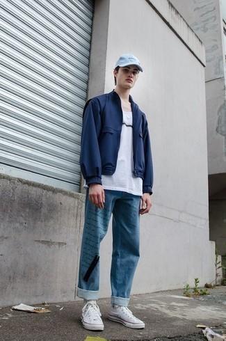 Blaue bedruckte Jeans kombinieren – 12 Herren Outfits: Vereinigen Sie eine dunkelblaue Bomberjacke mit blauen bedruckten Jeans, um mühelos alles zu meistern, was auch immer der Tag bringen mag. Weiße hohe Sneakers aus Segeltuch verleihen einem klassischen Look eine neue Dimension.