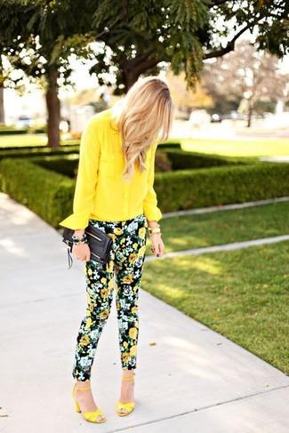 Wie kombinieren: gelbes Chiffon Businesshemd, schwarze enge Hose mit Blumenmuster, gelbe Leder Sandaletten, schwarze Leder Clutch