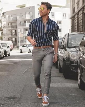 Wie kombinieren: dunkelblaues und weißes vertikal gestreiftes Businesshemd, graue enge Jeans, rotbraune Wildleder niedrige Sneakers, beige Ledergürtel