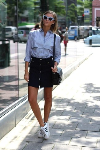 Wie kombinieren: hellblaues vertikal gestreiftes Businesshemd, schwarzer Rock mit Knöpfen, weiße und schwarze Leder niedrige Sneakers, schwarze Leder Umhängetasche