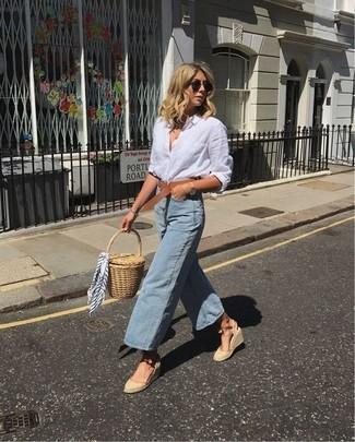 Wie kombinieren: weißes Leinen Businesshemd, hellblauer Hosenrock aus Jeans, hellbeige Keilsandaletten aus Segeltuch, beige Stroh Clutch