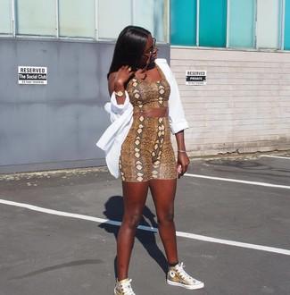 Wie kombinieren: weißes Businesshemd, braunes kurzes Oberteil mit Schlangenmuster, braune Radlerhose mit Schlangenmuster, goldene hohe Sneakers aus Leder
