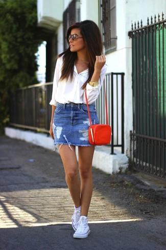 Wie kombinieren: weißes Businesshemd, blauer Jeans Minirock mit Destroyed-Effekten, weiße hohe Sneakers, orange Leder Umhängetasche