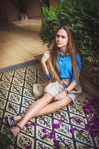 Wie kombinieren: blaues Businesshemd, grauer Falten Minirock, blaue Keilsandaletten aus Wildleder, hellbeige Leder Umhängetasche