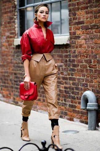 Damen Outfits & Modetrends 2020 für Herbst: Mit dieser Kombination aus einem roten Leder Businesshemd und einer braunen Karottenhose aus Leder werden Sie die ideale Balance zwischen Funktion und zeitloser Eleganz erreichen. Ergänzen Sie Ihr Look mit beige Leder Stiefeletten mit Ausschnitten. Ein toller Look für den Herbst.