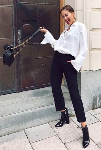 Schwarze Karottenhose kombinieren: trends 2020: Um ein frischen, lässiges Outfit zu erzeugen, wahlen Sie ein weißes Businesshemd und eine schwarze Karottenhose. Schwarze Leder Stiefeletten sind eine großartige Wahl, um dieses Outfit zu vervollständigen.