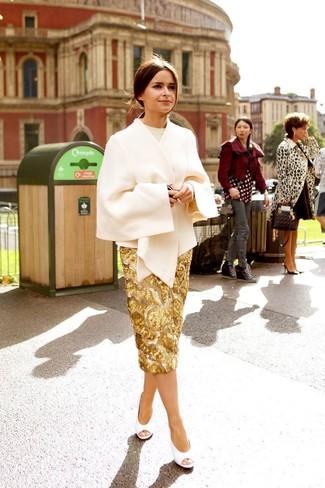 Wie kombinieren: hellbeige Cape Mantel, hellbeige Pullover mit einem Rundhalsausschnitt, goldener Paillette Bleistiftrock, weiße Leder Pumps mit Ausschnitten